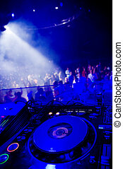 Djs turntable, blurred crowd on the background