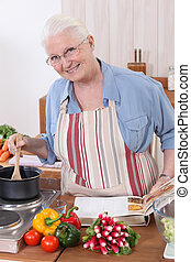 Elderly woman cooking with the help of a recipe