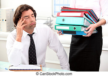 Office worker overwhelmed by load of work