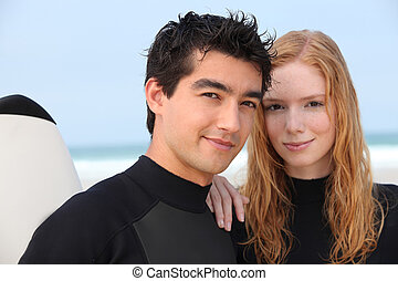 Young couple in wetsuits at the beach