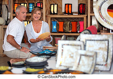 55 years old couple looking a plate in a handicrafts shop