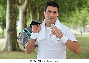Man drinking water after a run in the park