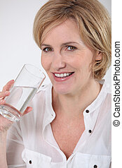 A middle age woman having a glass of water.