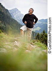 Active senior hiking in high mountains Swiss Alps