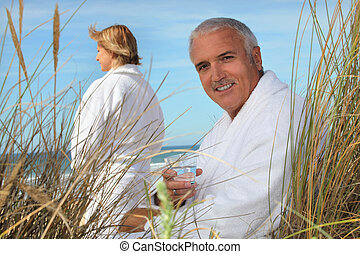 Couple at the beach in robes