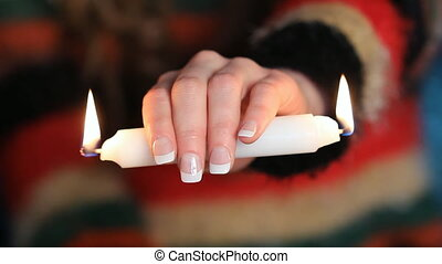 Burning the candle at both ends - A young woman holding a...
