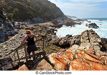 Woman hiking along the Rocky coastline