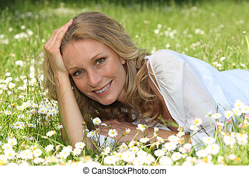 Woman lying in a grassy field