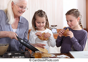 A grandmother cooking crepes for her granddaughters