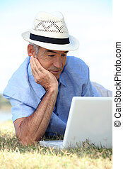 Elderly man laying in field with laptop