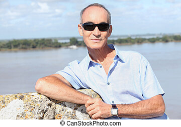 65 years old man in front of a river and some island