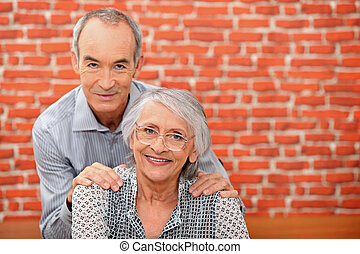 Older couple in front of a brick wall