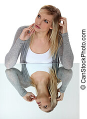 Pensive blond woman leaning on reflective surface