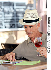Elderly man drinking a glass of rose in a cafe