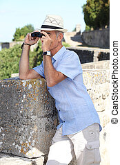 Man with binoculars and a hat