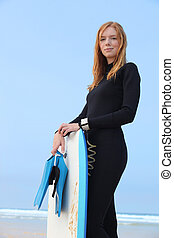 Woman stood in wetsuit with body-board