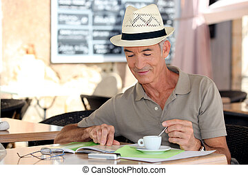 senior gentleman enjoying free time in cafe