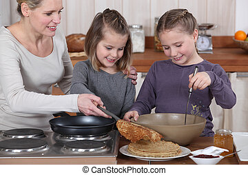 Woman cooking crepes with her daughters