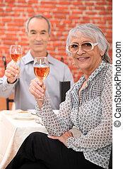 Elderly couple drinking wine in restaurant