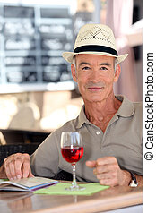 Older gentleman tourist drinking a glass of rose in a...