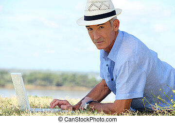 Senior man lying on the grass in front of laptop