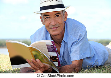 Elderly man reading a book outside
