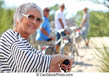 65 years old woman doing bike in the country with friends