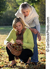 Mother and daughter gathering chestnuts in garden