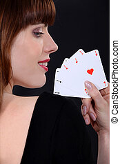 Woman poker player with four aces in hand