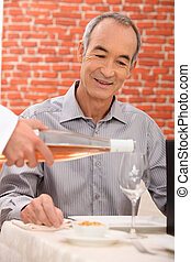 Man being served a glass of rose wine