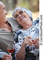 Elderly drinking wine.