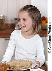Little girl holding a plate of crepes