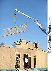 Crane lifting a wooden structure