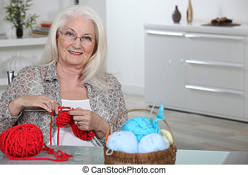 Old lady knitting in kitchen