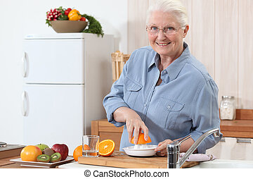 An old lady pressing oranges