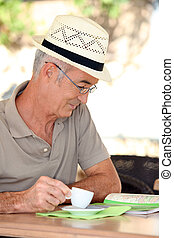 Retired man looking at a map while drinking coffee