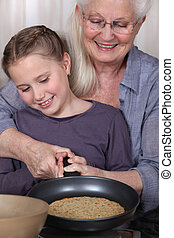 Girl and her granny cooking pancakes