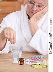 An old lady taking pills.