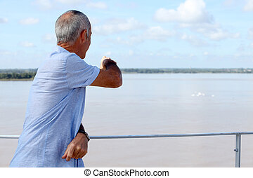 A mature man looking at the ocean.