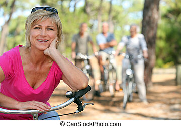 Older female cyclist riding with friends in the forest