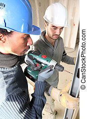 black and white carpenters at work with electric drill