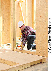 Builder constructing a house