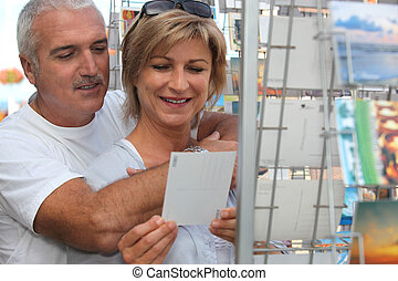 senior couple on vacation buying post cards