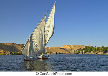 Typical sailing on the Nile. In the background sand hills and blue sky. (near Aswan, Egypt). Horizontally.