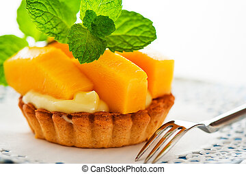 French tart with mango and vanilla pudding on white...
