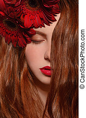 Redhead girl with red gerbera isolated on white