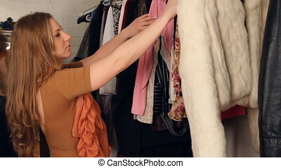 Young woman looks through clothes - Young woman looking...