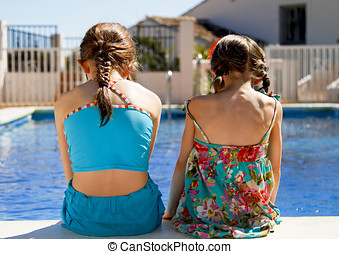 Two sisters stitting by the pool - Two little sisters...