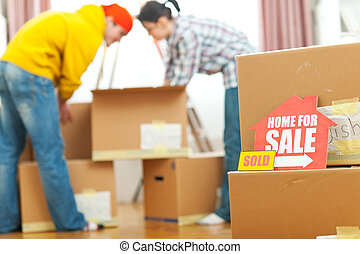 Home for sale sign with sold sticker and unpacking young family in background
