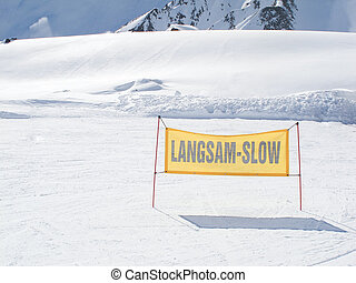 yellow warning sign on the ski piste
